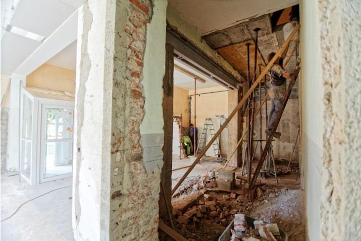 Bauarbeiter sind in einem Haus, das renoviert wird. Jetzt erfahren Sie, welche Rolle die 10-Prozent-Regelung bei außerordentlichen Mitgliederversammlungen spielt.
