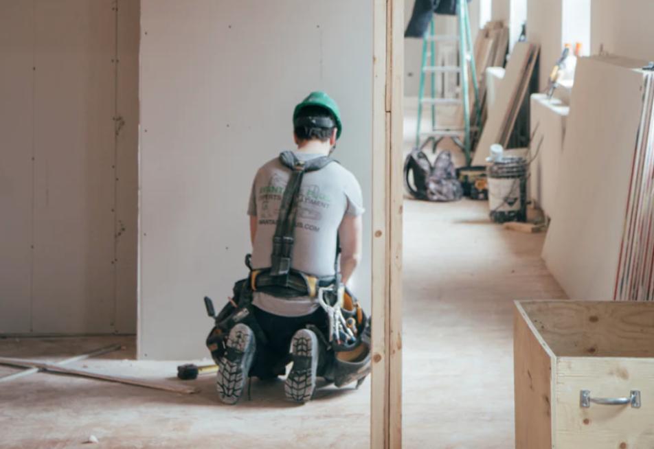 Ein Bauarbeiter kniet auf dem Boden und repariert eine Wand. In diesem Abschnitt geht es um die Höhe der Umlagen.
