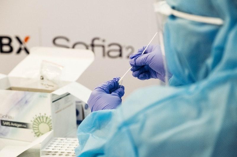 Eine Person in Schutzkleidung ist in einem Labor. Jetzt erfahren Sie, wie die Symptome einer Infektion mit Corona aussehen und wie weit Unternehmen bei der Entwicklung eines Impfstoffs sind.