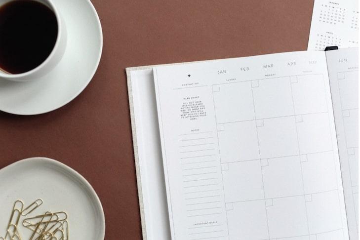 Auf dem Bild sind Papierklammern, eine Tasse Kaffee und ein Notizbuch. Auch eine Tagesordnung gehört auf die Einladung zur Mitgliederversammlung. In diesem Abschnitt erfahren Sie alle wichtigen Informationen dazu.