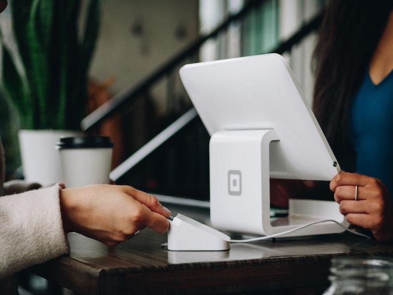 Wir sehen ein elektronisches Kassensystem, eine Frau bezahlt mit Kreditkarte. Vereine unterliegen der Kassenbon-Pflicht, wenn sie wirtschaftlich tätig sind und eine elektronische Registrierkasse benutzen.