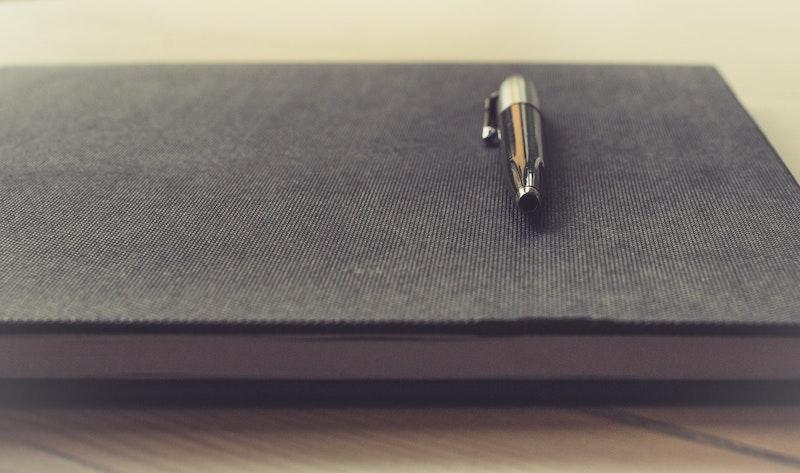 Auf dem Bild ist ein Buch, auf dem ein Stift liegt. Die Vereinssatzung regelt, wie der Vorstand zusammengesetzt ist.