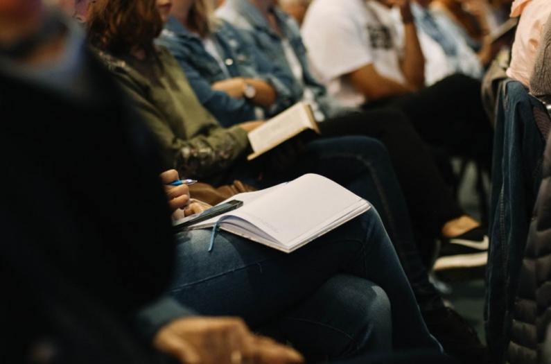 Menschen sitzen im Raum bei einer Versammlung und haben Notizblöcke auf ihren Schößen. In diesem Beitrag geht es um außerordentliche Mitgliederversammlungen in Vereinen