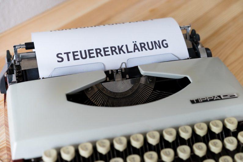 In einer Schreibmaschine ist ein Blatt Papier, auf dem das Wort Steuererklärung zu sehen ist. Nun erfahren Sie, was Vereine bei der Abgabe einer Steuererklärung beachten müssen und in welchen Fällen sie steuerpflichtig sind.