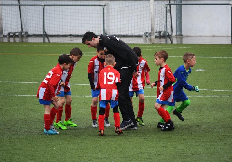 Ein Sporttrainer spricht auf dem Fußballfeld mit den Spielern. Jetzt erfahren Sie, bei welchen Tätigkeiten Vereine häufig die Übungsleiterpauschale vergeben.