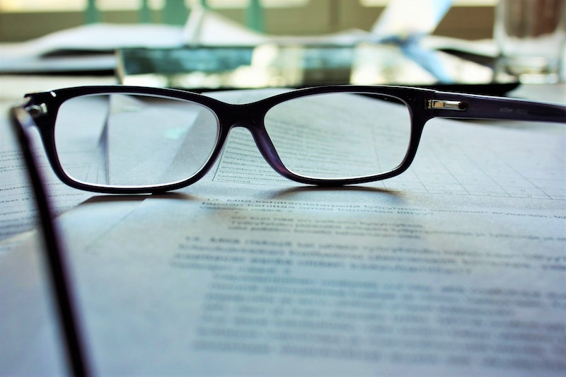 Auf dem Bild liegt eine Brille auf einem Stapel Dokumente. Sie erfahren jetzt, welche Vereinsstrafen es gibt und was genau in der Satzung geregelt werden sollte.