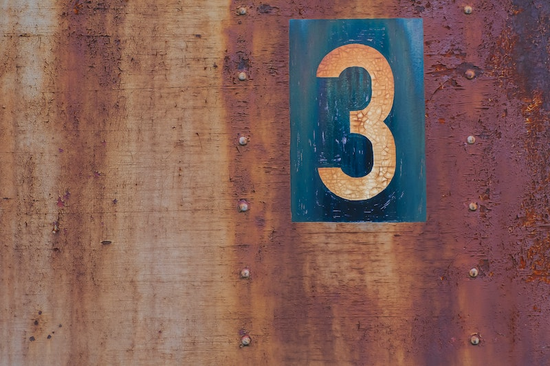 Auf einem rostigen Hintergrund steht die Nummer drei geschrieben. Wir verraten Ihnen drei Gründe, die gegen einen sofortigen Rücktritt eines Vorstandsmitglieds sprechen.
