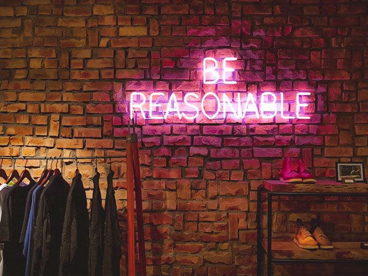 """Ein neonfarbener Schriftzug mit den Worten """"Be Reasonable"""" ist auf einer Backsteinwand angebracht. Der verantwortungsvolle Umgang mit dem Vereinsvermögen ist der erste und wichtigste Grundsatz, wenn Sie es in Aktien anlegen möchten."""