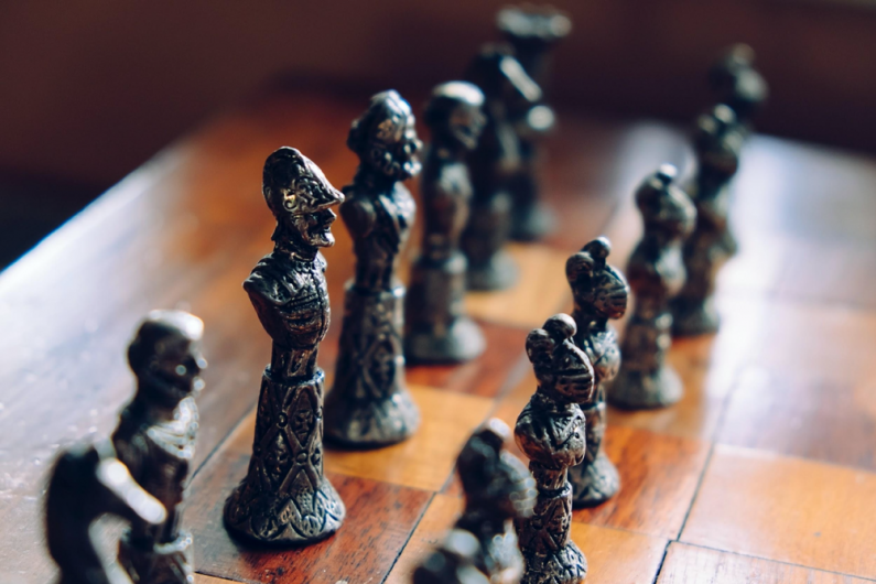 Schachfiguren stehen auf einem Schachbrett. Auch in Ihrem Verein sollten Sie sich gut überlegen, wer den Verein nach außen vertritt. Verschiedene Satzungsregelungen werden in diesem Artikel erklärt.]