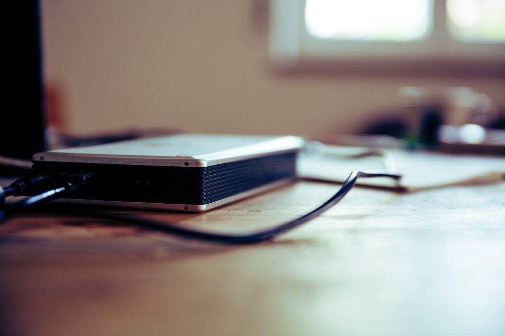 Eine externe Festplatte liegt auf einem Schreibtisch. Ihre Vereinsunterlagen sollten Sie regelmäßig auf einem physischen Speichermedium sichern.