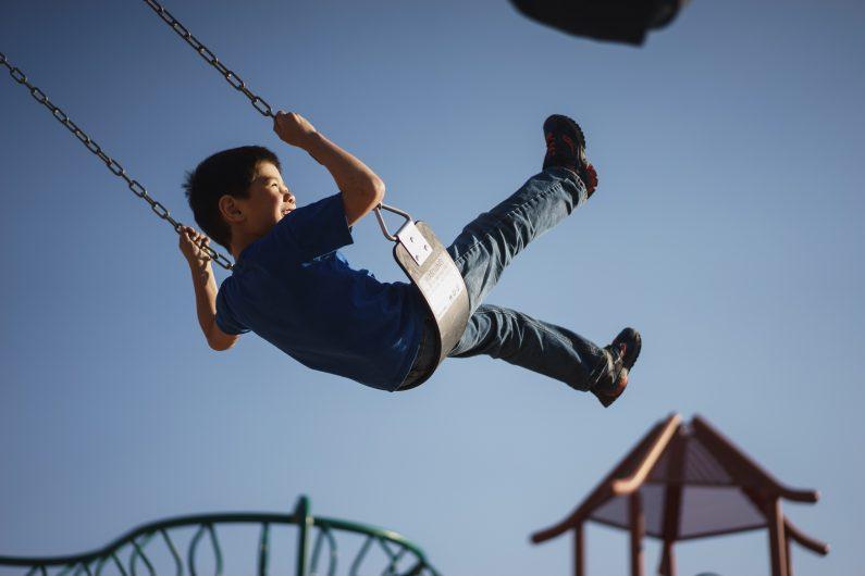 Ein Junge schaukelt auf einem Spielplatz. Die Fragen, wann und wie Eltern von minderjährigen Vereinsmitgliedern haften, wird in diesem Beitrag beantwortet.