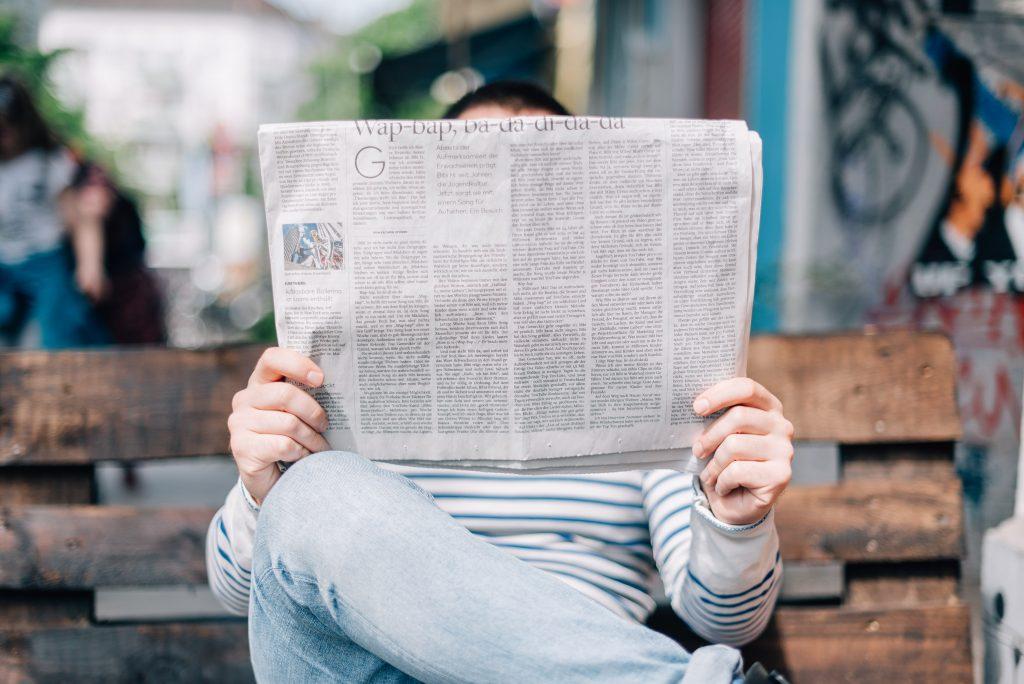 Eine Person sitzt auf einer Bank und liest eine Zeitung. Wenn Sie mit Ihrer Pressemitteilung erfolgreich sind, dürfen Sie auf einen Artikel in der Lokalzeitung hoffen.