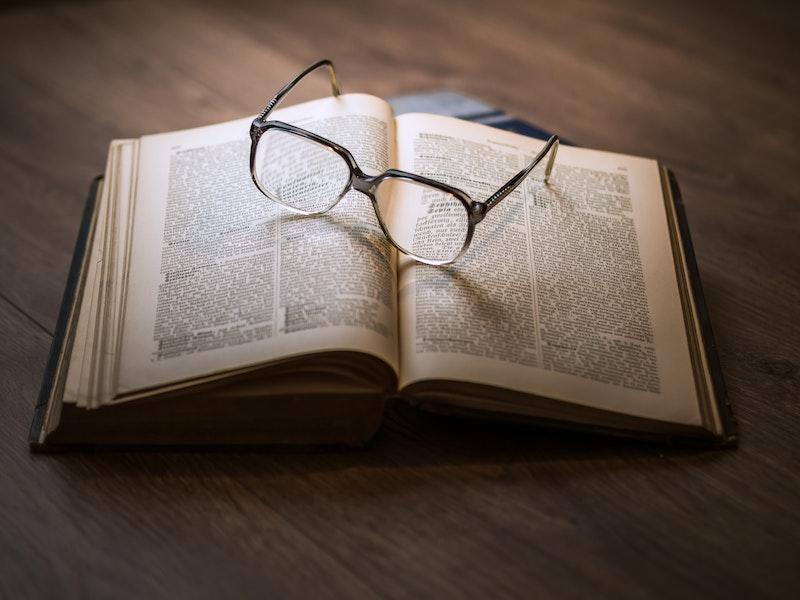 Ein Buch liegt auf einem Tisch, darauf ist eine Brille. Im folgenden Kapitel erfahren Sie die häufigsten Gründe für eine Vereinsauflösung.
